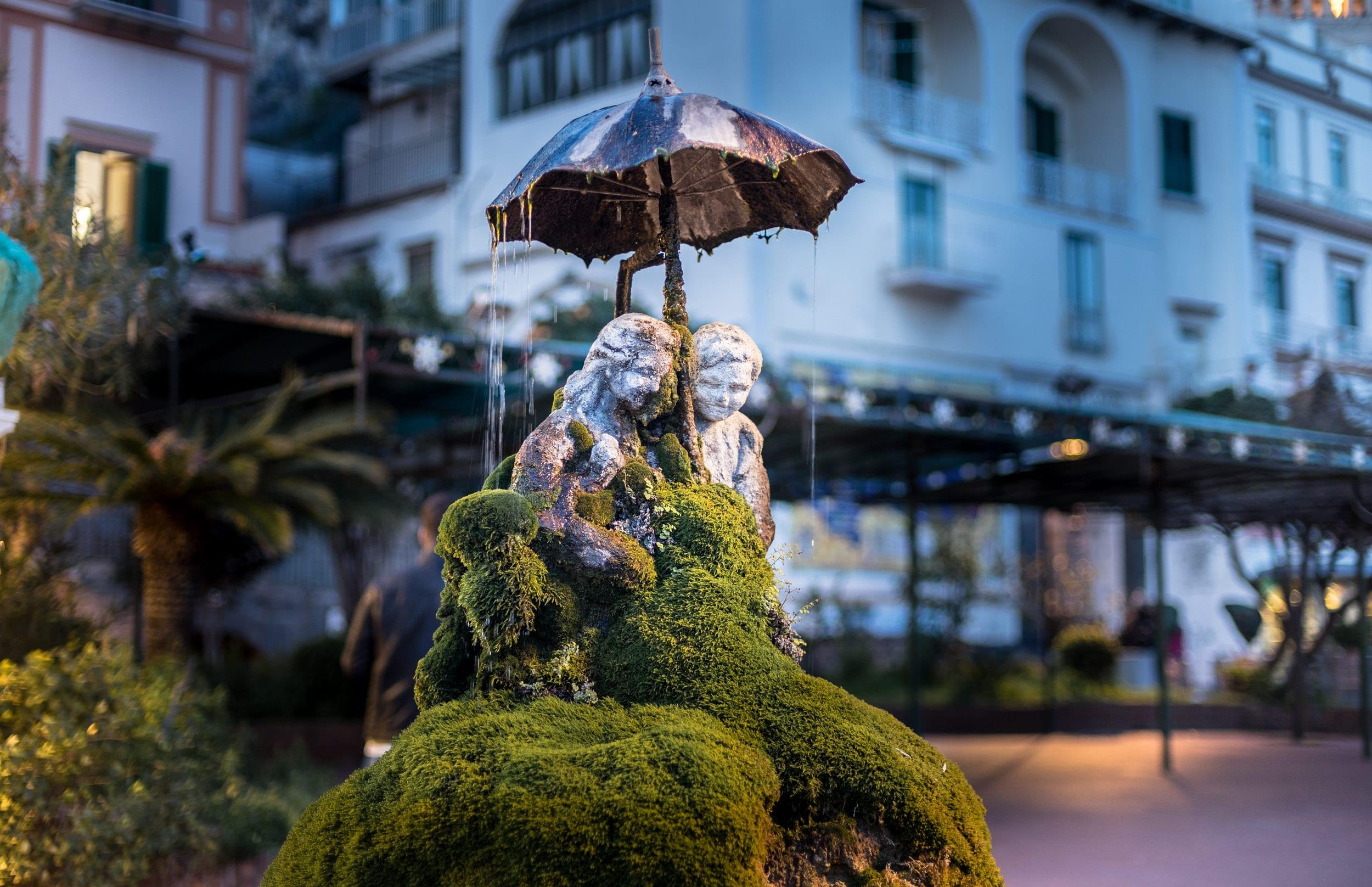 На самом виду. На остановке автобусов. Есть этот прекрасный фонтан в Амальфи. Двое под дождем. Внизу фонтана плавают золотые рыбки а люди почти не обращают на фонтан внимания. Кстати, это один из немногих фонтанов на побережье Амальфи из которого не получится пить. Остальные фонтаны, прктически все питьевые.  Лучшая фишка — сменяемость красок. Зеленый мох покрывает эту парочку под зонтом только зимой. Летом и весной мох желтый и рыжий. Все потому что он сильно выгорает